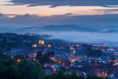 A romantic photograph of Hexham, Northumberland, at dusk, with its Abbey floodlit.