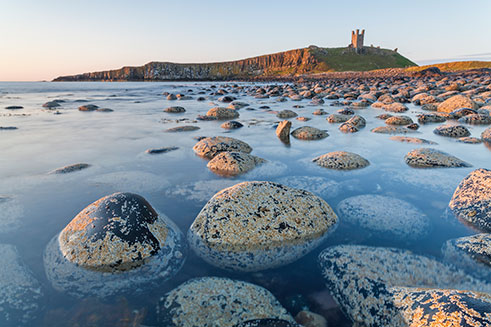 A stunning image of Dunstanburgh Castle, on the Northumberland coast, at sunrise.