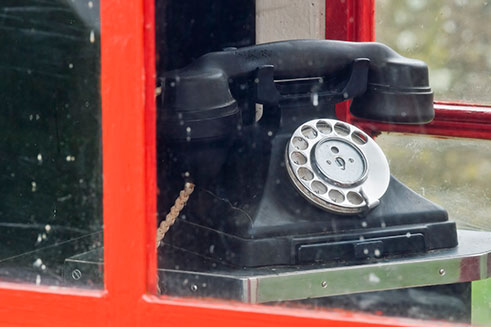 An old-fashioned telephone in a red telephone box in historic Tyneham village in Dorset.