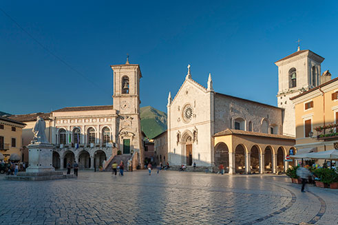 A travel image of the town of Norcia, in Perugia, Italy, lit by bright sunshine.